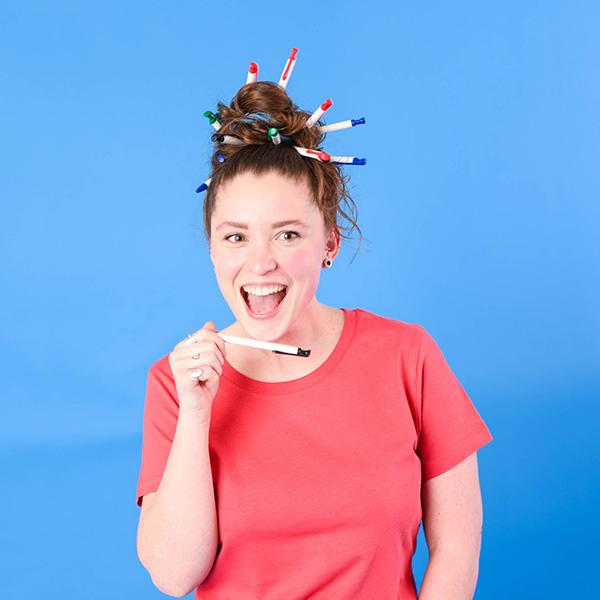 Femme avec des stylos dans les cheveux