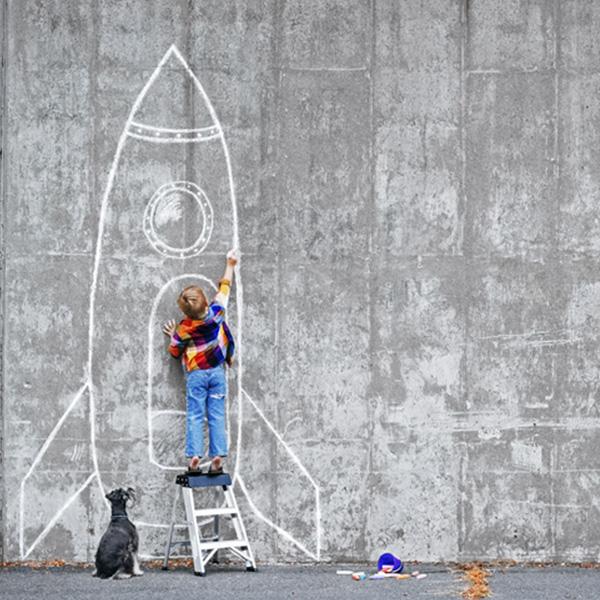 Enfant sur un escabot qui dessine une fusée